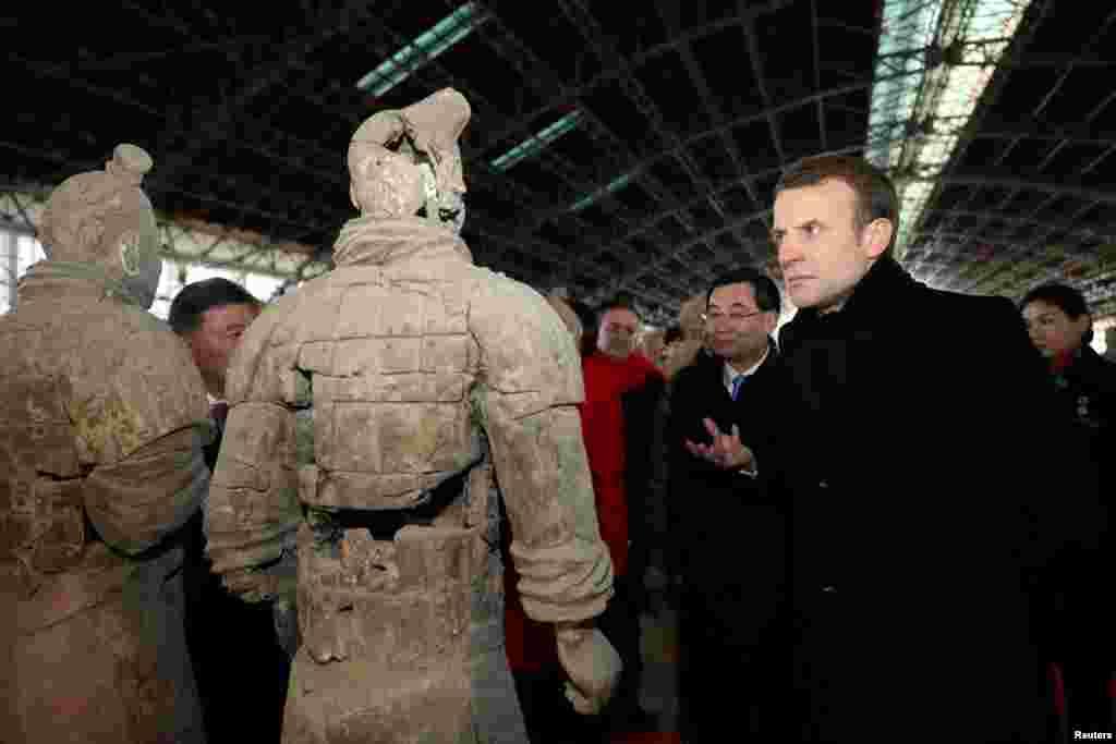2018年1月8日,法国总统马克龙在中国陕西省西安市参观秦代兵马俑博物馆,近距离观察兵马俑。 马克龙携夫人布丽吉特开始对中国进行正式访问,在西安参观了兵马俑、有几百年历史的大雁塔和清真寺。