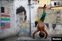 A member of the Acorda Capoeira (Awaken Capoeira) group prepares for a performance for tourists in the Rocinha favela in Rio de Janeiro, Brazil, July 25, 2016.