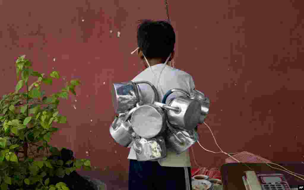 A tea delivery boy with empty tea pots attached to a rope hang on to his forehead, collects empty tea cups and tea-pots from an outdoor telephone stand in Rangoon, Burma.