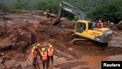 Petugas penyelamat berusaha melakukan penggalian di lokasi tanah longsor di desa Malin, negara bagian Maharashtra, India (30/7).