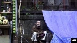 印度孟买一位贫困男子坐在他的临时窝棚外(资料照片)