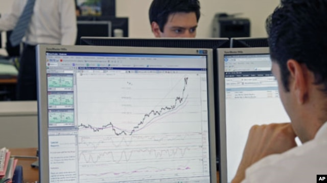 Traders at the Saxo Banque study their screens in their offices in Paris, August 10, 2011