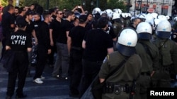 Riot police try to stop members of the Golden Dawn party from unloading food from a vehicle in Athens, Greece, May 2, 2013.