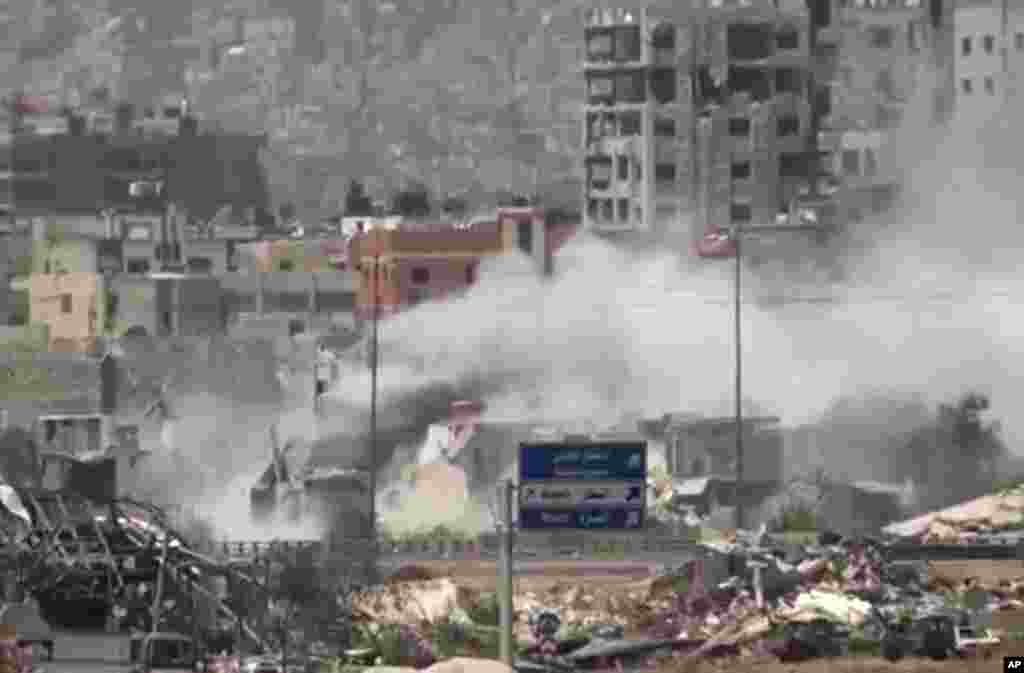 This image taken from video obtained from Ugarit News shows shelling of the Al-Qaboun neighborhood in rural Damascus, Syria, July 15, 2013.