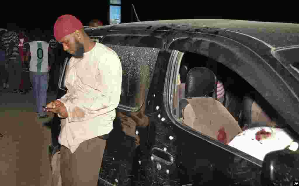 A man uses his mobile phone next to the vehicle in which Sheikh Ibrahim Ismael and three others were killed near Mombasa, Kenya, Oct. 3, 2013.
