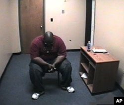 In 'Scenes of a Crime,' Adrian Thomas waits alone in the interrogation room of the Troy, New York police station on Sept. 21, 2008 after being accused of killing his child.