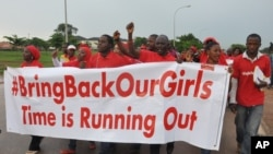 FILE - People shout slogans and hold a banner during a demonstration in Abuja, Nigeria.