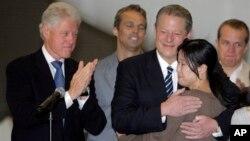 빌 클린턴(왼쪽) 전 미국 대통령은 지난 2009년 8월 북한에 억류된 미국인 여기자 두 명의 석방을 위해 북한을 방문했습니다. 미국 캘리포이나주 버뱅크의 밥 호프 공항에 도착한 클린턴 전 대통령이 로라 링 기자와 앨 고어 전 부통령이 포웅하는 모습을 지켜보고 있다.