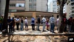 Archivo. Gente espera en una cola para comprar pan en Caracas, Venezuela, el 23 de marzo de 2018.