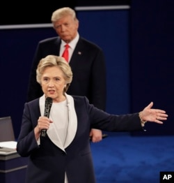 FILE - Republican presidential nominee Donald Trump listens to Democratic presidential nominee Hillary Clinton during the second presidential debate at Washington University in St. Louis, Oct. 9, 2016.