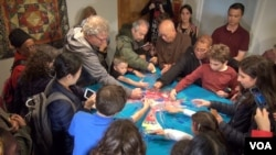 People of all ages are dismantling the sand mandala, an integral part of the ancient ritual art. (VOA/ J. Soh)