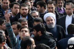 An Iranian man takes a selfie, hoping to capture Iranian President Hassan Rouhani in his picture during a rally marking the 37th anniversary of the Islamic revolution in Tehran on Feb. 11, 2016.