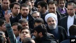 Un homme iranien, à gauche, prend une selfie en essayant d'avoir le président Hassan Rouhani, juste avec le turban blanc, sur la photo lors d'un rassemblement commémorant le 37e anniversaire de la révolution islamique, à la rue Azadi (Freedom) à Téhéran, en Iran , 11 février 2016.