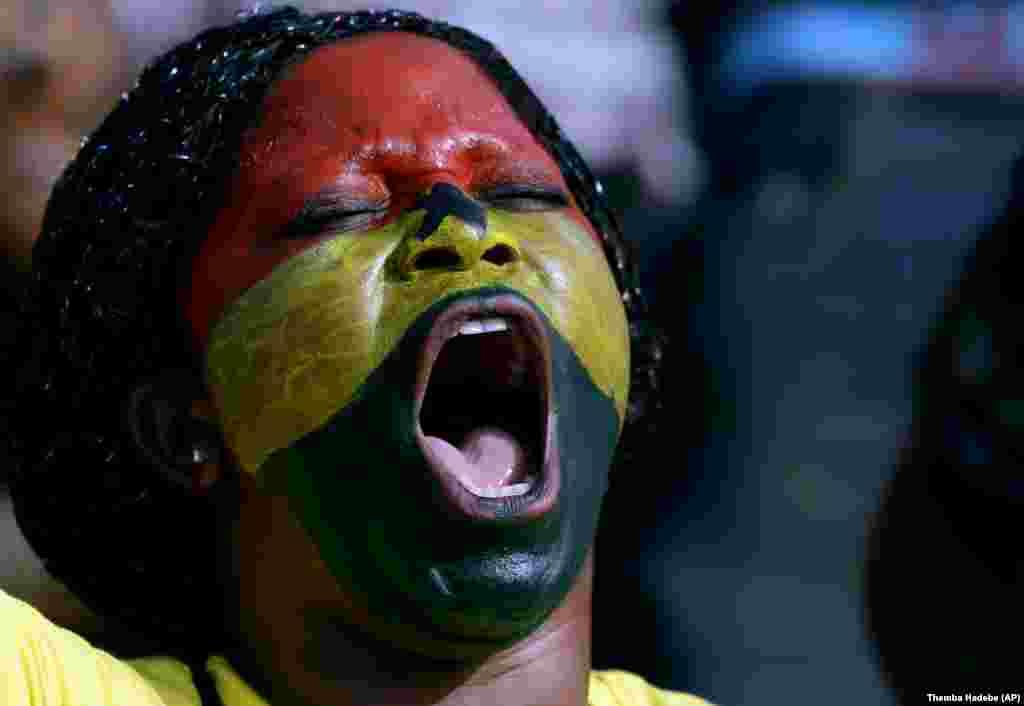 Seorang penggemar sepakbola dari Ghana dengan wajah dicat berteriak menyemangati tim negaranya dalam pertandingan Grup C Piala Afrika di Mongomo, Guinea Ekuatorial (19/1). (AP/Themba Hadebe)