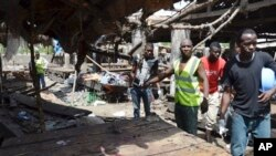Rescue workers at the site of a suicide bomb attack at a market in Maiduguri , Nigeria, Tuesday, June 2, 2015. Boko Haram attacked the northeastern Nigerian city of Maiduguri with deafening explosions from the west and a suicide bombing near the center that witnesses said killed as many as 20 people. (AP Photo/Jossy Ola)