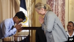 Secretary of State Hilary Rodham Clinton bows in response to Vannak Anan Prum of Cambodia, before presenting him with a plaque for his work to end human trafficking, during the release of the 2012 Trafficking in Persons Report at the State Department in