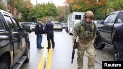 A SWAT police officer and other first responders respond after a gunman opened fire at the Tree of Life synagogue