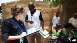 An international observer take notes at a polling place in Daura, Nigeria, Saturday, April 16, 2011.