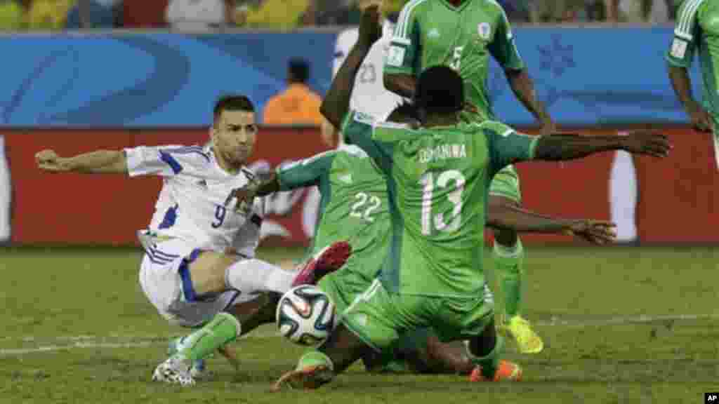 Nigeria's Juwon Oshaniwa, right No 13, blocks a shot by Bosnia's Vedad Ibisevic.