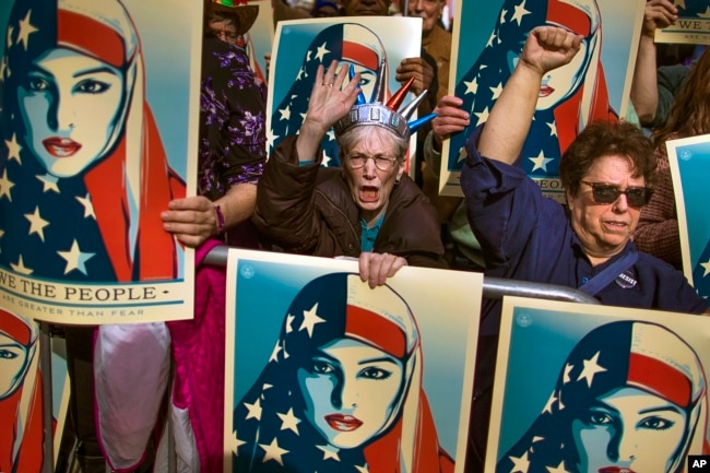 FILE - In this Feb. 19, 2017 file photo, people carry posters during a rally against President Donald Trump's executive order banning travel from six Muslim-majority nations, in New York's Times Square.