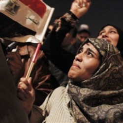 An Egyptian woman among many celebrating in Tahrir Square in Cairo