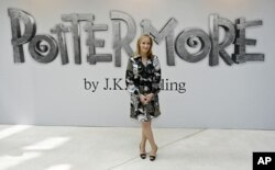 FILE - British author J.K. Rowling poses for photographers as she announces her new website project Pottermore at the Victoria and Albert Museum in London, June 23, 2011