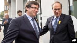 El ex líder catalán, Carles Puigdemont, izquierda, es recibido por el actual presidente regional catalán, Quim Torra, quien viajó a Bélgica.