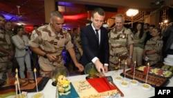 Le président français Emmanuel Macron coupe un gâteau couvert des couleurs du drapeau français lors d'un dîner de Noël avec quelque 700 soldats français de la force anti-djihadiste française sur la base aérienne française de la force Barkhane à Niamey, Ni