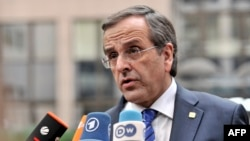 FILE - Greek Prime Minister Antonis Samaras answers journalists' questions as he arrives to attend a European Council meeting at the EU headquarters in Brussels, Oct. 24, 2013