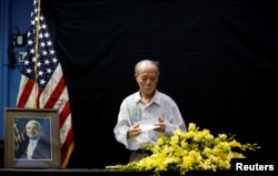 Vietnamese veteran Pham Minh Chuc, 81, pays respect after he wrote in a condolence book near a portrait of U.S. Senator John McCain (R-AZ) at the U.S. embassy in Hanoi, Vietnam, Aug. 27, 2018.
