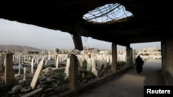 FILE - A woman walks at a cemetery in Douma, in the eastern suburbs of Damascus, Syria, March 9, 2021.