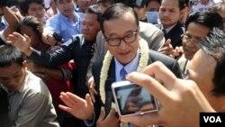 ທ່ານ Sam Rainsy ຫົວໜ້າພັກກູ້ຊາດກໍາປູເຈຍ ກ່າວຕໍ່ສື່ມວນຊົນ ຢູ່ນອກປະຕູເຂົ້າສະໜາມບິນກ່ອນທີ່ທ່ານຈະເລີ້ມຍ່າງໄປໃນນະຄອນພະນົມເປັນ ຂອງກໍາປູເຈຍໃນວັນທີ 16 ສິງຫາ 2013. (Robert Carmichael for VOA)