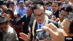 Sam Rainsy talks to the media outside the airport gate before beginning his walk into Phnom Penh, Cambodia, August 16, 2013. (Robert Carmichael for VOA)