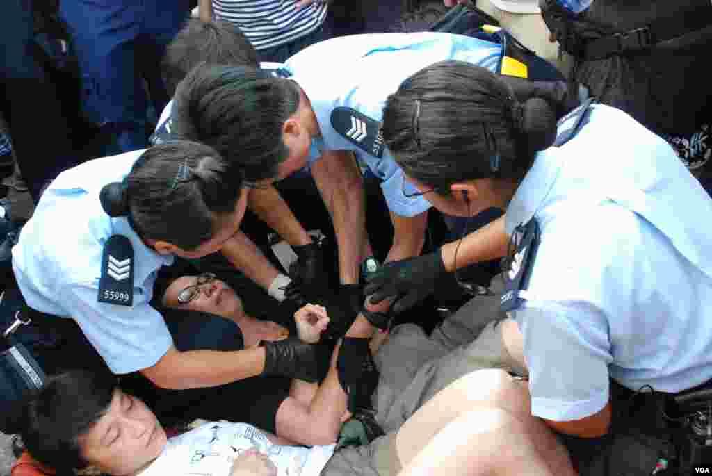 數名警員合力解開靜坐人士緊扣的雙手