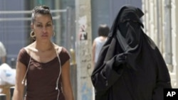 Two women, one wearing the niqab, a veil worn by the most conservative Muslims that exposes only a woman's eyes, right, walk side by side, in the Belsunce district of downtown Marseille, central France, Friday June 19, 2009. The French government's spokes