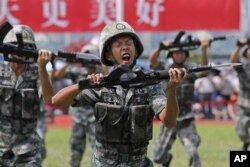 ANggota Tentara Pembebasan Rakyat China (PLA) memperagakan keterampilan mereka di pangkalan angkatan laut Pulau Stonecutter, Hong Kong, pada peringatan 22 tahun penyerahan Hong Kong ke China, 30 JUli 2019. (Foto: dok).