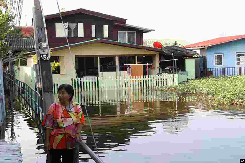 A woman stands in floodwater in a residential area of Bangkok, October 27, 2011. (VOA - D. Schearf)