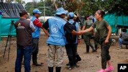 Un observador de Naciones Unidas estrecha la mano de un rebelde de las FARC, antes de un encuentro en La Carmelita, cerca de Puerto Asis, en el suroeste de Putumayo, miércoles 1 de marzo de 2017.