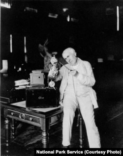 Thomas Edison in his West Orange library examining a strip of film.