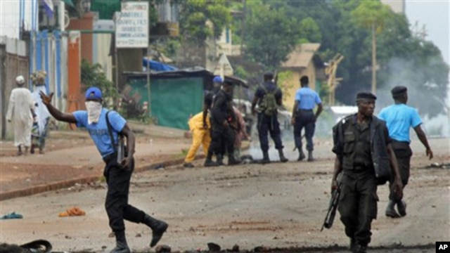 Guinean police carrying automatic weapons clear the mostly Peul suburb of Bambeto in Conakry, Guinea, 16 Nov.2010, as groups of UFDG youth set up barricades. A de-facto curfew is in effect in the area, residents staying inside, one day after it was announ