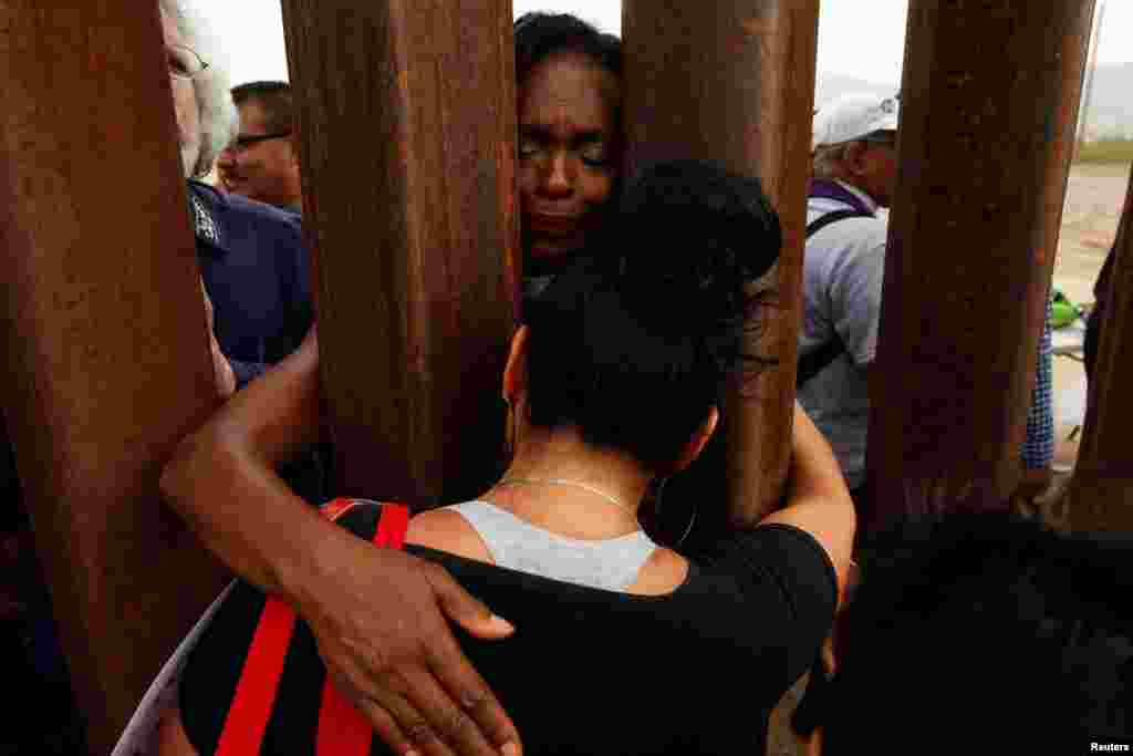 "Women embrace through the border fence during the ""Interfaith Service for Justice and Mercy at the Border"" to demand the U.S. government to end the separation of immigrant children from their parents at the border, in Ciudad Juarez, Mexico."