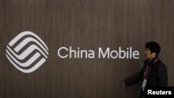 一名男子路过中国移动的标志