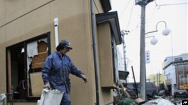 A resident cleans up tsunami debris in his destroyed house Tuesday, March 15, 2011, in Soma city, Fukushima prefecture, Japan, four days after a massive earthquake and tsunami struck the country's north east coast. (AP Photo/Wally Santana)