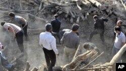 Жители разбирают завалы зданий в поисках людей, выживших во время землетрясения в городе Варзакан на северо-западе Ирана. 12 августа 2012 г.