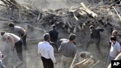 伊朗民眾星期天在伊朗西北部一個被地震摧毀的村莊搜尋有用的物品