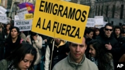 "FILE - Demonstrators carry signs reading ""We are forced to leave"" and ""They send us away"" during a protest against unemployment among young people and the emigration produced by the financial crisis in Madrid, Spain, April 7, 2013."