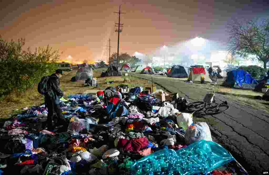Evacuees sift through a pile of clothing at an encampment in a Walmart parking lot in Chico, California, Nov. 17, 2018. More than 1,000 people remain listed as missing in the worst-ever wildfire to hit the U.S. state.