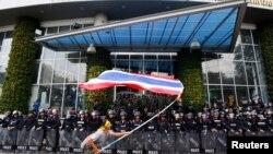 Người biểu tình chống chính phủ phất cờ trước cảnh sát chống bạo động và binh sĩ Thái Lan tại thủ đô Bangkok.