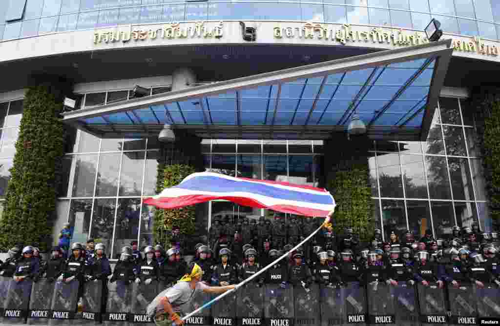 An anti-government protester waves a national flag in front of riot police officers and soldiers guarding the entrance of the National Broadcast Services of Thailand (NBT) television station, in Bangkok, May 9, 2014.
