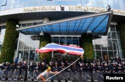 在位于曼谷的泰国全国广播服务电视台大楼前,一名反政府抗议人士在镇暴警察前挥舞国旗。 (2014年5月9日)